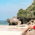 A girl sitting barefoot on the stone of Dreamland Beach Bali